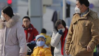 Diese Menschen in Peking schützen sich mit Gesichtsmasken vor der neuen Lungenkrankheit.
