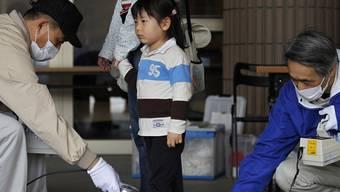 Ein Mädchen wird im April 2011 in einem Evakuierungszentrum in Fukushima auf Strahlenbelastung untersucht (Archiv)