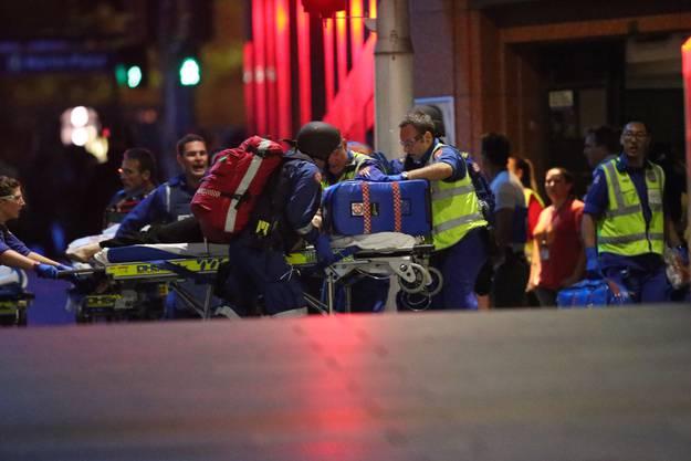Nach der Stürmung des Cafés: Sanitäter bringen eine verletzte Geisel zu einem Krankenwagen.