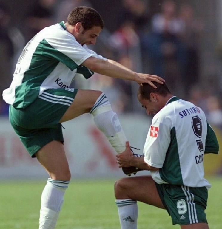 Giorgio Contini putzt seinem Teamkollegen Giuseppe Mazzarelli in der Meistersaison 2000 nach einem Treffer die Schuhe. (© Keystone/Michele Limina)