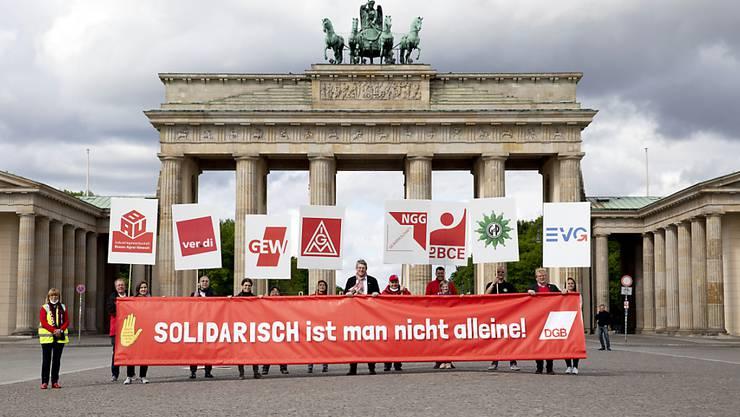 """""""Solidarisch ist man nicht allein!"""" 1. Mai-Demonstranten vor dem Brandenburger-Tor in Berlin."""