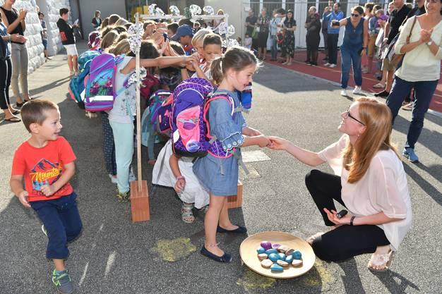 Klassenlehrerin Denise Frankiny empfängt die neuen Erstklässler. Zuvor krochen diese durch das Spalier der älteren Schüler und ein symbolisches Baustellentor.
