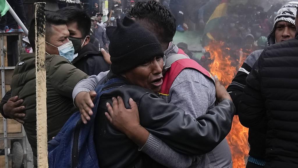 Regierungsgegnerische Koka-Bauern umarmen sich nach einem Zusammenstoß mit der Polizei in der Nähe des Kokamarktes. Foto: Juan Karita/AP/dpa