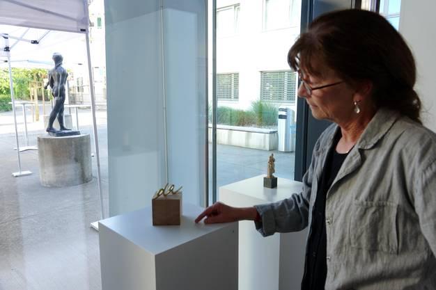 Ursula Rutishauser mit einem ihrer geschnittenen Wortfragmente - mit Blick auf eine Skulptur von Eduard Spörri (Bild ub)