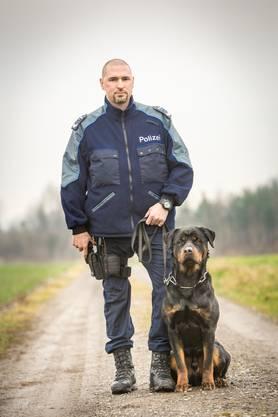 Stillgestanden! Wachtmeister Niedermann hält die rechte Hand an seiner Faustfeuerwaffe und an der linken steht sein bester Kollege bereit: Rottweiler Gysmo.