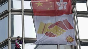"""Der Extremkletterer Alain Robert rollte am Freitag in Hongkong an einem Wolkenkratzer ein """"Friedensbanner"""" aus."""