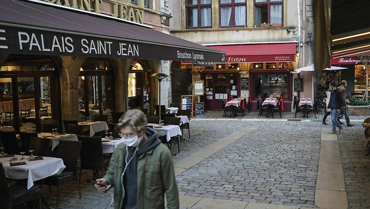ARCHIV - Ein Mann trägt eine Maske und geht an den leeren Tischen und Stühlen von Restaurants vorbei. Die Corona-Pandemie hat in den fünf größten Volkswirtschaften Europas das Verbrauchervertrauen nachhaltig erschüttert. Foto: Laurent Cipriani/AP/dpa