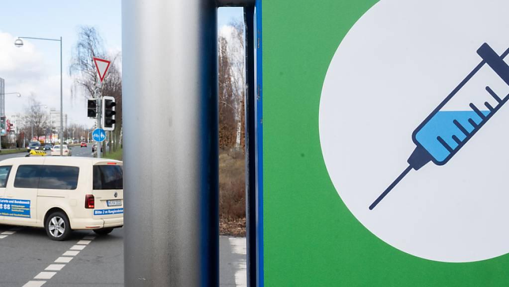 Ein Schild mit einer Spritze hängt an der Zufahrt zum Impfzentrum auf dem Messegelände.