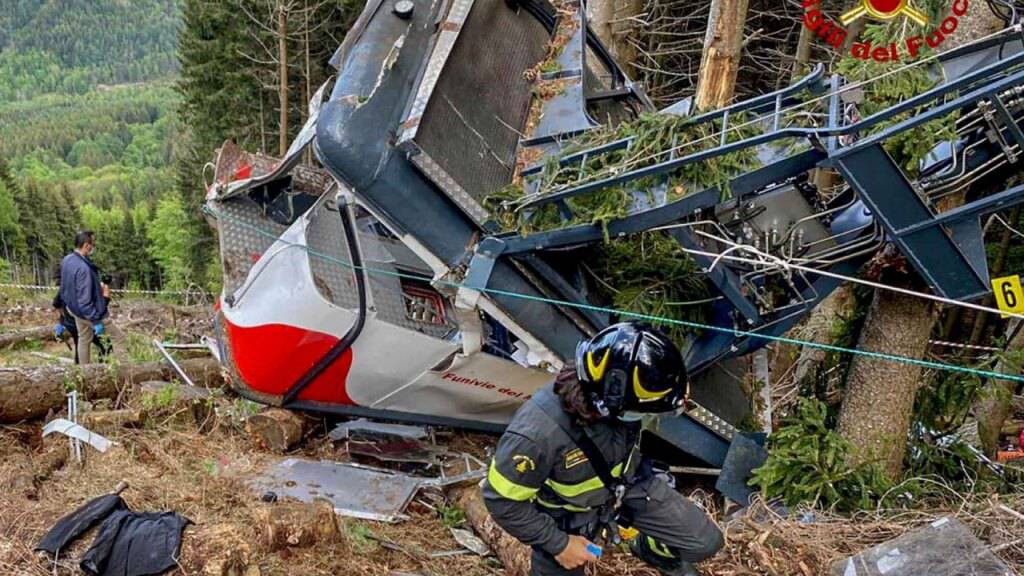 HANDOUT - Rettungskräfte arbeiten am Wrack einer abgestürzten Gondel, die in einem Waldstück liegt. Nach dem Seilbahnunglück in Italien soll die Unglücksgondel mit einem Hubschrauber abtransportiert werden. Foto: Uncredited/Vigili del Fuoco Firefighters/AP/dpa - ACHTUNG: Nur zur redaktionellen Verwendung im Zusammenhang mit der aktuellen Berichterstattung und nur mit vollständiger Nennung des vorstehenden Credits