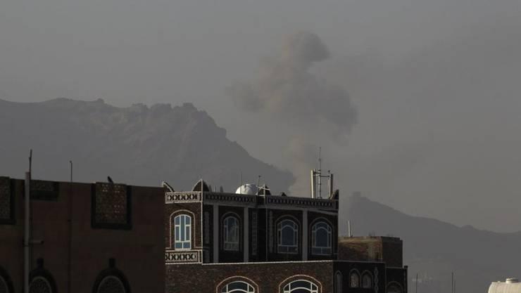 Über Gebäuden in der jemenitischen Hauptstadt Sanaa steigt Rauch auf. Ungeachtet der Friedensgespräche in Genf soll die von Saudi-Arabien geführte Militärallianz erneut Luftangriffe gegen Stellungen der schiitischen Huthi-Miliz geflogen haben