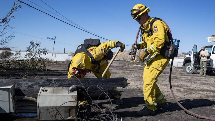 Feuerwehrleute untersuchen einen bei einem Buschfeuer umgestürzten Strommasten bei Santa Clarita in Kalifronien. (Archivbild)