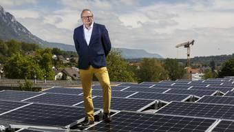 Christian Herzog vor der Photovoltaik Anlage auf dem Firmendach.