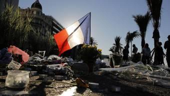 Gedenken an die Opfer des Terrorattentates von Nizza: Eine französische Flagge und Blumen am Boden des Boulevard des Anglais.