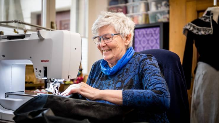 Lotti Tschumi sitzt auch heute noch gerne an der Nähmaschine. Im Hintergrund eines der ersten Kostüme, das sie genäht hat.