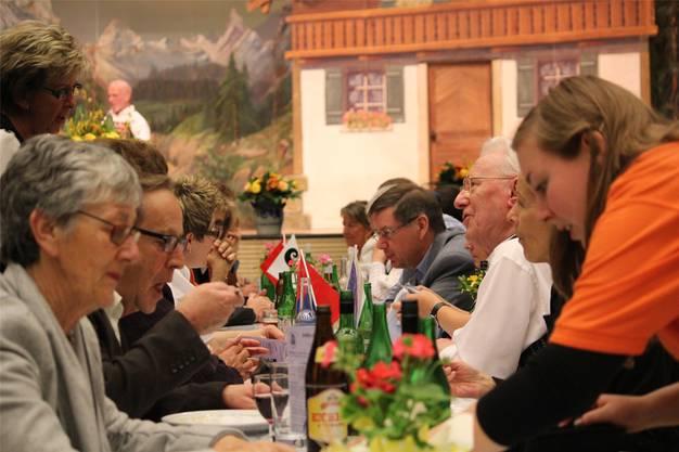 Die Besucherinnen und Besucher geniessen Speis und Trank.