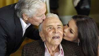 Der 102-jährige Kirk Douglas (Mitte) wird von seinem Sohn Michael Douglas (links) und seiner Schwiegertochter Catherine Zeta-Jones geküsst. (Archiv)