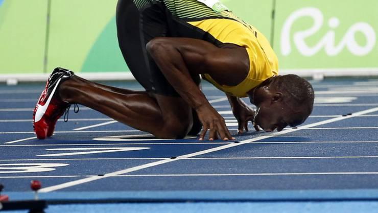 Usain Bolt küsst nach seinem Triumph über 200 m die Ziellinie