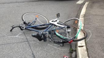 Eine Velofahrerin wird von einem Auto angefahren und stürzt zu Boden (Symbolbild).