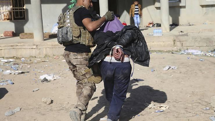 Ein irakischer Soldat führt einen Mann an der Mossul-Front ab, der der Kollaboration mit der Terrormiliz Islamischer Staat (IS) verdächtigt wird. (Bild von Ende November 2016)