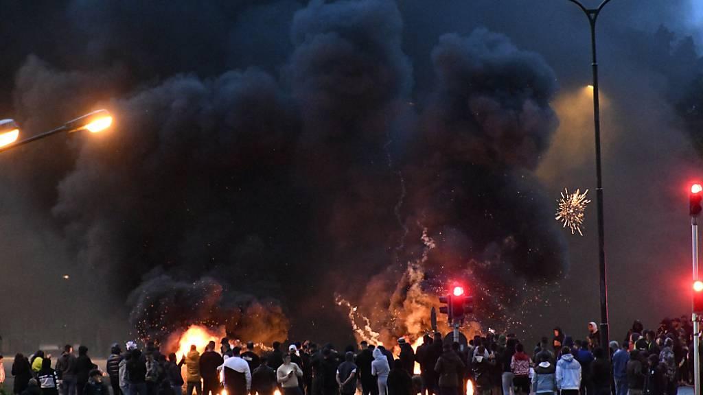 Demonstranten stehen auf einer Straße vor brennenden Reifen. Nachdem rechtsextreme Aktivisten in Malmö einen Koran verbrannten, kam es zu massiven Protesten und Unruhen. Foto: Uncredited/TT NEWS AGENCY/AP/dpa