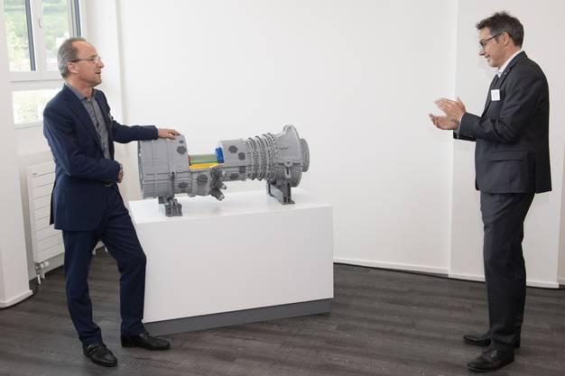 Jürg Schmidli, VR-Präsident und Geschäftsführer von Ansaldo Energia Switzerland (rechts), erhält von Bruno Koller, Kirkbi Real Estate, die Gasturbine aus Lego.