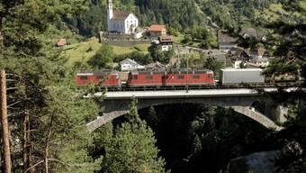 Ein Güterzug mit mehreren Lokomotiven passiert auf der Gotthardstrecke bei Wassen eine Eisenbahnbrücke. Der Güterverkehr durch die Schweizer Alpen hat im ersten Halbjahr 2019 abgenommen - auf der Strasse ebenso wie auf der Schiene. (Archivbild)