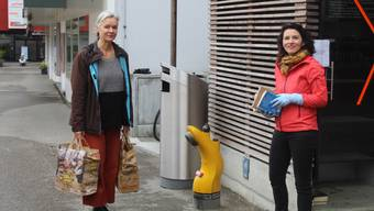Katja Leudolph (links) und Amira Hafner beim Bestücken des Bücherschrankes beim Marktplatz.