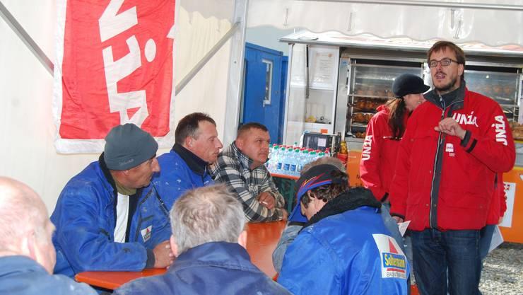 Gewerkschafter Serge Gnos von der Unia Region Aarau spricht vor Bauarbeitern in Widen.