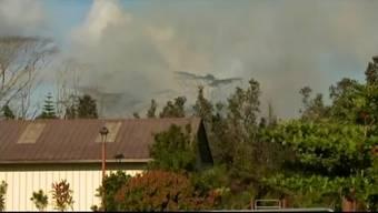 Rauch, Asche und Lava drangen aus einem Riss in einer Strasse in Puna auf Big Island.