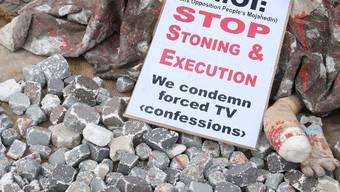 Eine Frau demonstriert gegen die Steinigung