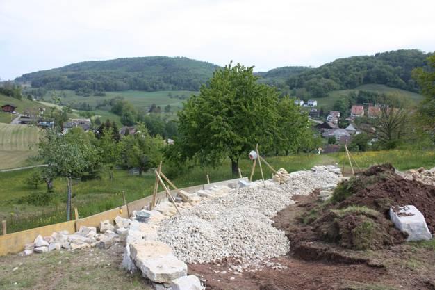 Das Hangniveau wird mit kleineren Kalksteinen ausgeglichen und so entsteht ein Trockenstandort für spezielle Pflanzen.