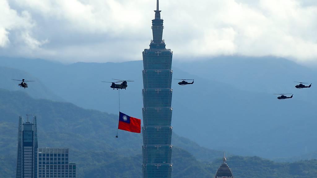 Ein Militärhubschrauber zieht eine riesige Taiwan-Fahne hinter sich her und fliegt vor den Feierlichkeiten des Nationalfeiertag am Hochhaus «Taipei 101» vorbei. Foto: Daniel Ceng Shou-Yi/ZUMA Press Wire/dpa