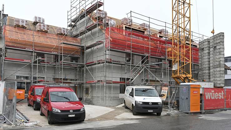 Auf dem Dach des Ärztehauses werden Ziegel verlegt, im Innern wird an Böden und Wänden gearbeitet.
