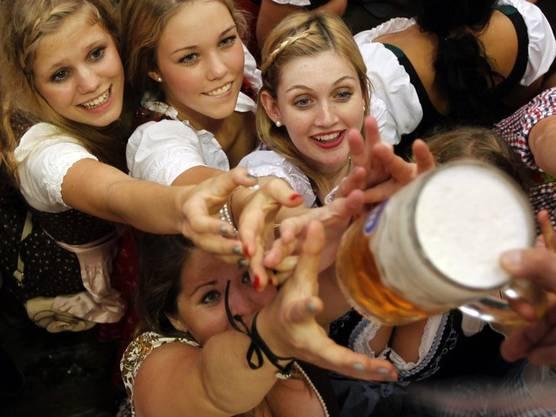 Frauen strecken sich nach einem Mass Bier am ersten Tag des diesjährigen Oktoberfestes in München
