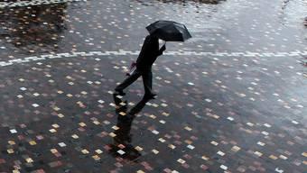 Ein Fussgänger in Athen trotzt dem Regen (Archivbild)