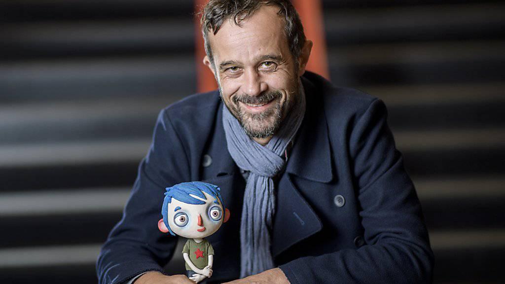 """Regisseur Claude Barras mit der Hauptfigur aus seinem Animationsfilm """"Ma vie de Courgette"""". Nach mehreren Auszeichnungen und einer Oscar-Nomination wurde der Streifen auf der Frankfurter Buchmesse als beste Kinderbuch-Verfilmung geehrt. (Archivbild)"""