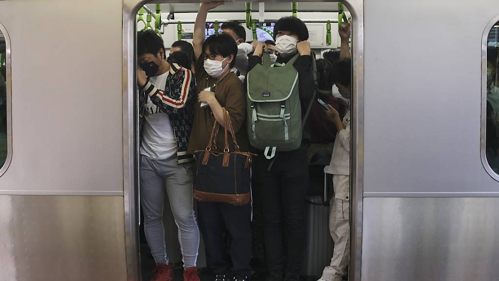 Pendler drängen sich in Tokio in einen Zugwaggon, nachdem ein starkes Erdbeben in der Nacht zum Donnerstag (Ortszeit) die Region Tokio erschüttert und Züge und U-Bahnen vorübergehend lahmgelegt hat. Bei dem Erdbeben sind laut Berichten japanischer Medien mindestens 32 Menschen verletzt worden. Foto: Kiichiro Sato/AP/dpa
