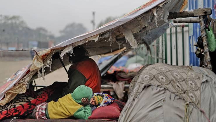 In der Armutsfalle? Ein Wintermorgen in Neu-Delhi, Indien, ein 7-Jähriger liegt neben seiner Schwester