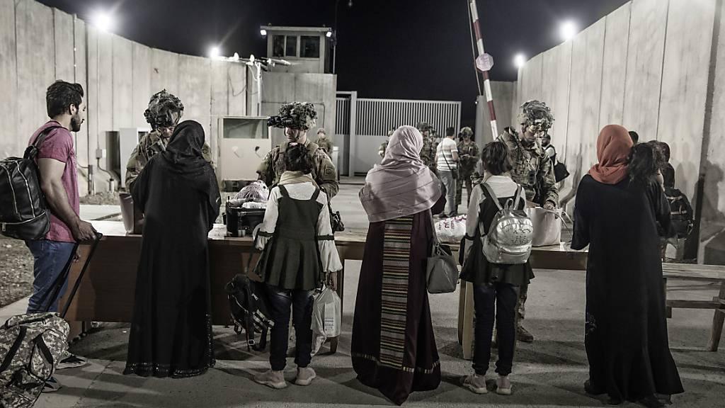 dpatopbilder - HANDOUT - Soldaten der 82. Luftlandedivision der US-Army helfen Menschen während der Evakuierung auf dem Flughafen Kabul. Inzwischen haben die Taliban eigenen Angaben zufolge mehrere Tore am Flughafen unter ihre Kontrolle gebracht. Foto: Staff Sgt. Victor Mancilla/U.S. Marine Corps/AP/dpa - ACHTUNG: Nur zur redaktionellen Verwendung und nur mit vollständiger Nennung des vorstehenden Credits