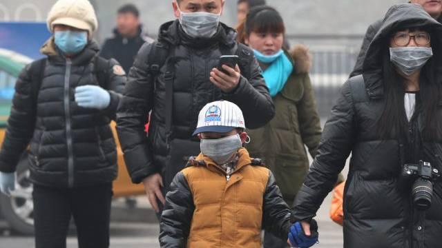 Bewohner Pekings tragen wegen schlechter Lunft einen Mundschutz