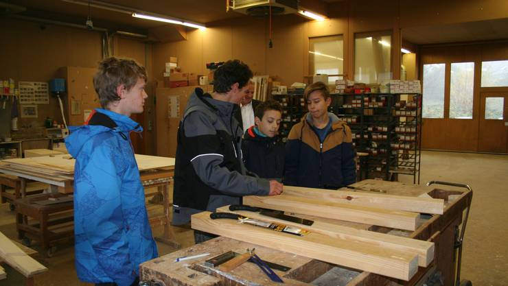 Drei Schüler der Kreisschule Biberist versuchen sich am Sägen in der Schreinerei Strausak Holzbau AG.
