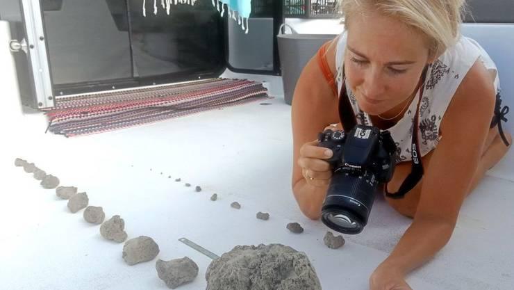 Die Seglerin Larissa Brill mit einer Auswahl an Bimssteinen aus dem riesigen Gesteinsteppich, der auf Australien zutreibt.