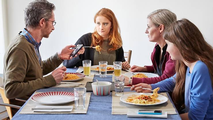 Vater, Mutter, zwei Teenager-Töchter beim Spaghetti-Essen. In Zug müsste diese Familie, egal was die beiden Eltern verdienen, deutlich weniger Steuern zahlen als in der Stadt Neuenburg. (Symbolbild)