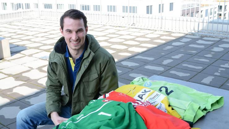 Simon Schelling mit Trikots aus seinen vier Stationen im Handball.