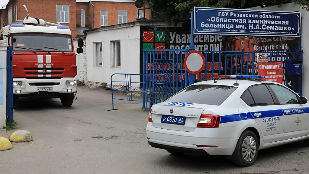 Ein Feuerwehrauto und ein Polizeiauto stehen am Eingang des Semashko- Rjasan  Provinzkrankenhauses, wo in der Nacht ein Feuer in einer Intensivstation ausgebrochen war. Foto: Alexander Ryumin/TASS/dpa Foto: Alexander Ryumin/TASS/dpa