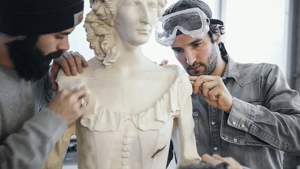 Der Künstler Inigo Gheyselinck (rechts) und seine Assistenten arbeiten an einer Statue von Madame Marie Tussaud. Die Holzfiguren sollen den Schweizer Rohstoff bei den Konsumenten wieder beliebter machen. (Archivbild)