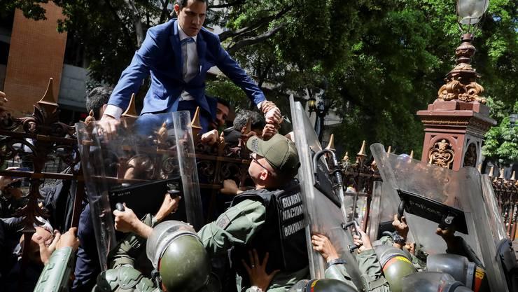 Der venezolanische Oppositionsführer Juan Guaidó versucht über einen Zaun das Parlament zu erreichen. Streitkräfte verhindern das.