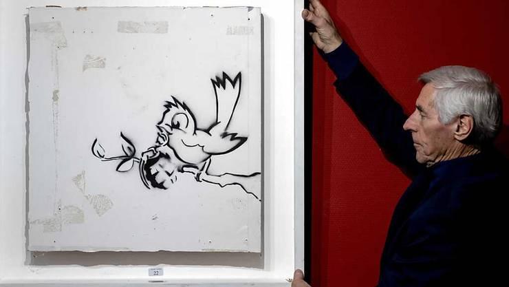 Das Bild «Bird with Grenade» («Vogel mit Granate») des Künstlers Banksy im Auktionshaus Hessink's. Foto: Sander Koning/ANP/dpa - ACHTUNG: Nur zur redaktionellen Verwendung im Zusammenhang mit einer Berichterstattung über das Bild «Bird with Grenade» («Vogel mit Granate») des Künstlers Banksy und nur mit vollständiger Nennung des vorstehenden Credits