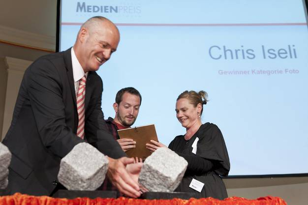 az-Fotograf Chris Iseli (Mitte) erhält den Preis von Thomas Müller, Präsident des Vereins Medienpreis Aargau-Solothurn und Nicole Aeby, Fachjury-Leiterin Foto.