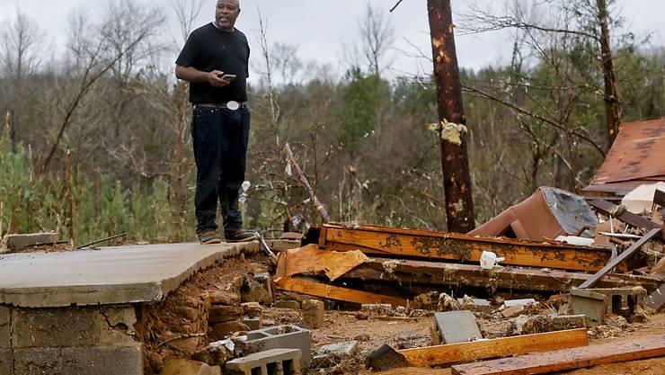 Ein Mann betrachtet die Überreste eines von einem Sturm im Bundesstaat Alabama zerstörten Hauses.
